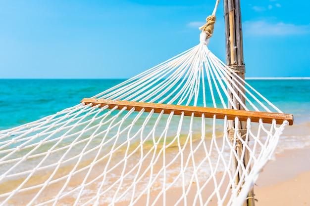 Amaca bianca vuota intorno all'oceano della spiaggia del mare per il concetto di vacanza di viaggio di piacere