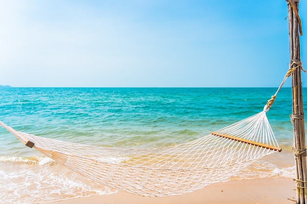 Empty white hammock around sea beach ocean for leisure travel vacation concept