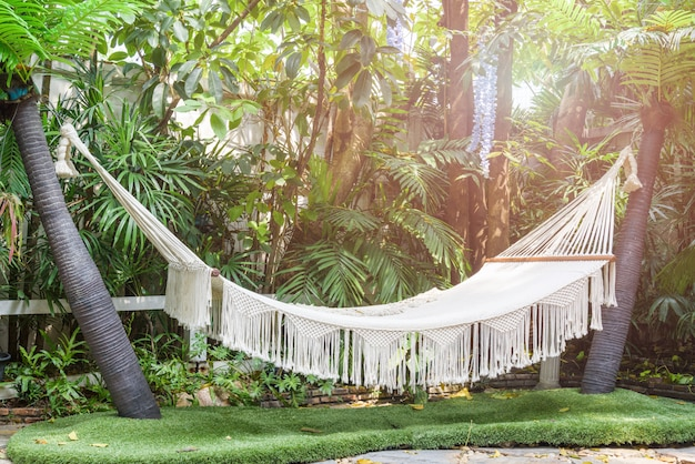 Empty white hammock hanging between palm trees in the garden