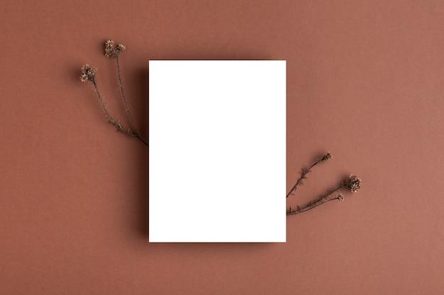 Empty white invitation card or business card mockup on a brown table
