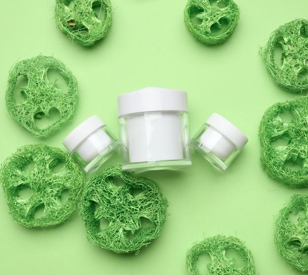녹색 배경에 화장품을 위한 빈 흰색 항아리. 크림, 젤, 혈청, 광고 및 제품 판촉용 포장. 조롱, 평면도