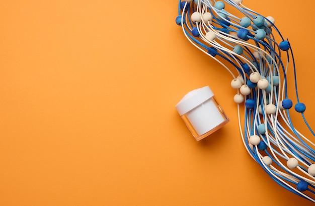 주황색 배경에 화장품을 위한 빈 흰색 항아리. 크림, 젤, 혈청, 광고 및 제품 판촉용 포장. 조롱, 평면도