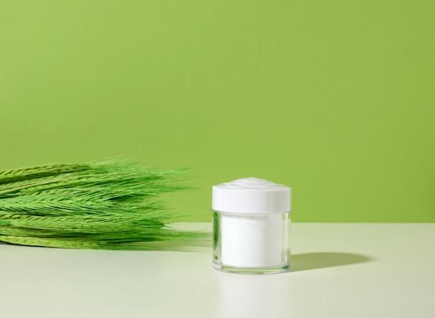 흰색 테이블, 녹색 배경에 화장품을 위한 빈 흰색 항아리. 크림, 젤, 혈청, 광고 및 제품 판촉용 포장. 조롱