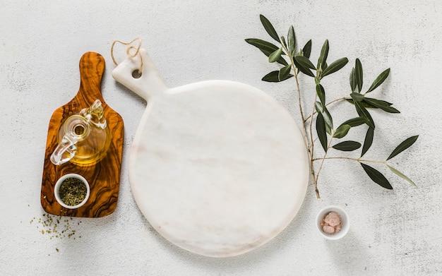 空の白い大理石のまな板とオリーブの木の枝