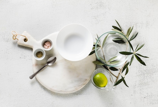 Empty white marble cutting board and olive tree branch