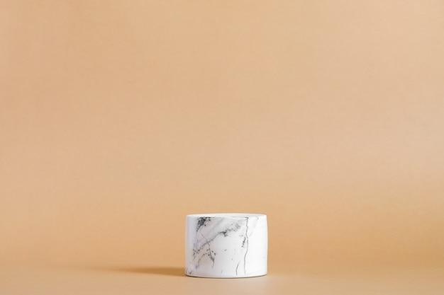 パステルベージュの空の白い大理石の表彰台