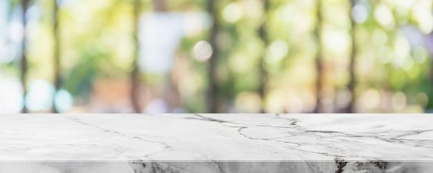 空の白い大理石の石のテーブルトップとぼやけたガラス窓のインテリアレストランのバナーは抽象的な背景をモックアップします-あなたの製品を表示したりモンタージュしたりするために使用できます。