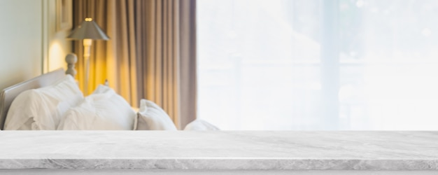 Empty white marble stone table top and blurred living room in home interior with curtain window