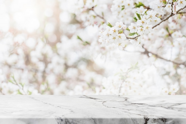 Empty white marble stone table top and blurred sakura flower tree in garden background with vintage filter - can used for display or montage your products.