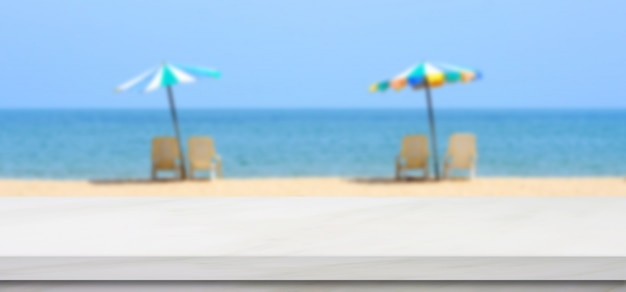 Empty white marble table over blur blue sky and sea beach with colourful umbrella