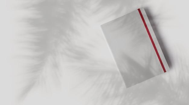 중성 회색 콘크리트 배경에 부드러운 그림자가 있는 빈 흰색 노트북 모형.