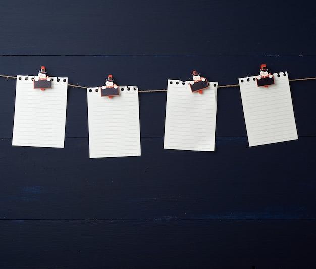 装飾的な休日の洗濯はさみに掛かっている空の白いノート用紙