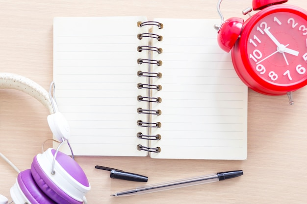 Empty white notebook with pen, alarm clock and headphone.