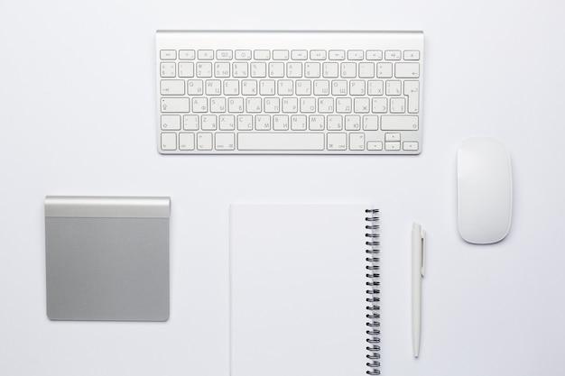 Пустой белый блокнот с пером на рабочем месте с клавиатурой и тачпадом