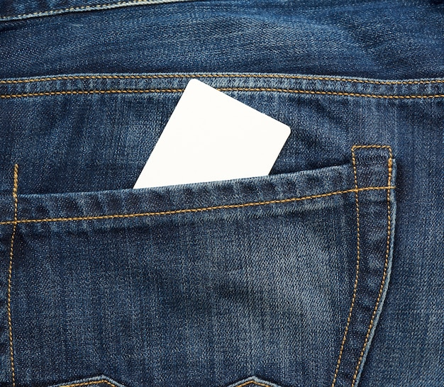 Empty white paper card is in the back pocket of blue jeans