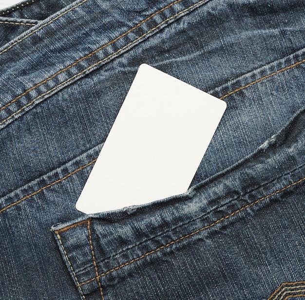 Пустая белая бумажная карточка находится в заднем кармане синих джинсов