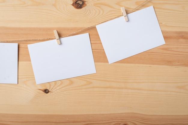 Пустые белые бумажные карточки, прикрепленные к веревке прищепками
