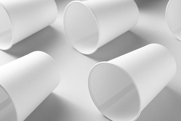 灰色の背景に空の白い紙コップの背景。廃棄物ゼロ。上面図