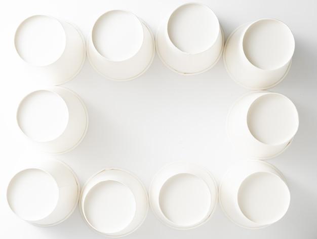 白の背景に空の白い紙コップの背景。廃棄物ゼロ。上面図
