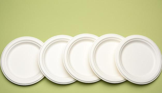 Пустые одноразовые тарелки из белой бумаги на зеленом фоне, вид сверху. концепция отказа от пластика, охрана окружающей среды