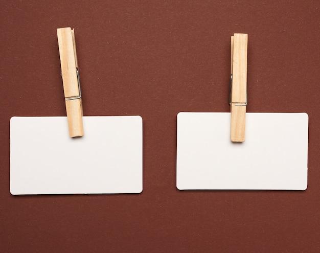 Пустые белые бумажные прямоугольные визитки с деревянными прищепками