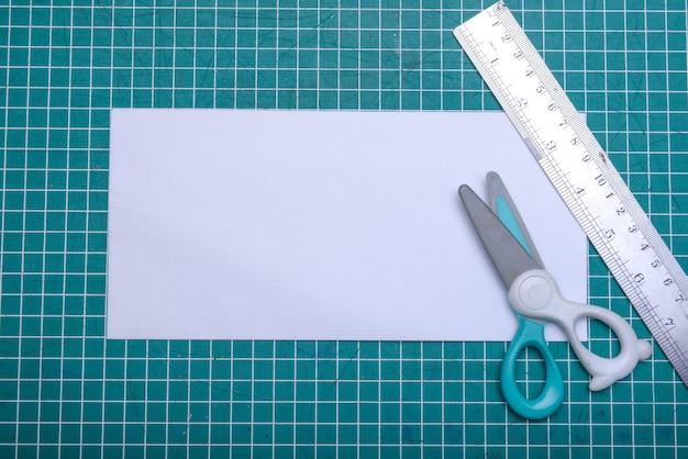 Пустая белая бумага с ножницами и линейкой на коврике для резки. пустой белый документ для копирования пространства