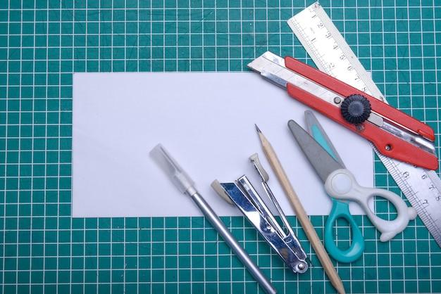 Пустая белая бумага с фиксатором на коврике для резки. пустой белый документ для копирования пространства