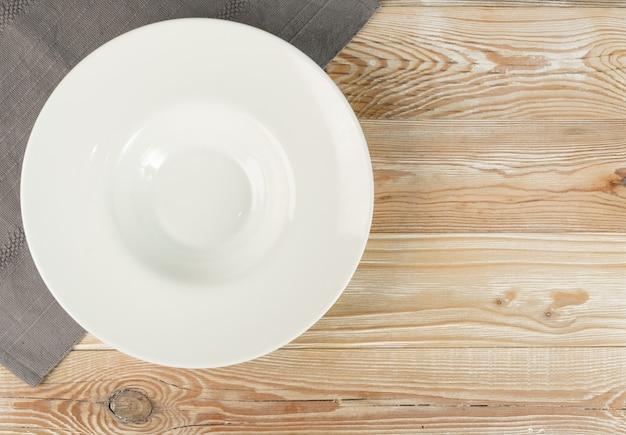 木製のテーブルトップビューの空の白いパスタプレート