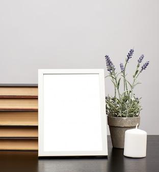 Empty white photo frame, stack of books