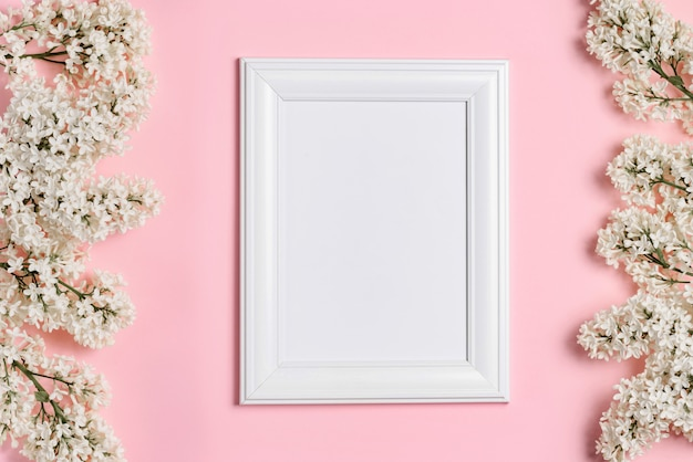 Empty white photo frame and white lilac flowers on a pink wall.