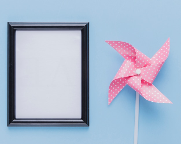 Empty white photo frame with pink pinwheel over blue backdrop