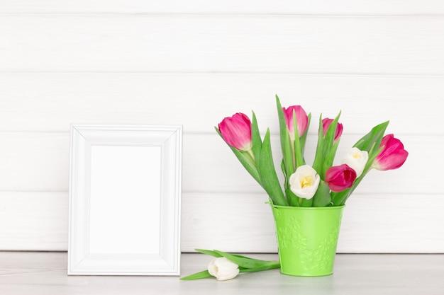 테이블에 튤립 꽃 부케와 빈 흰색 사진 프레임 라이트 소박한 인테리어
