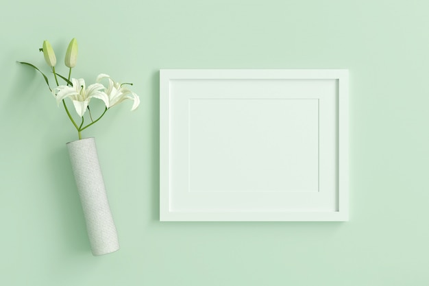 Empty white picture frame for insert text or image inside with white flower decorate on mint green pastel color.