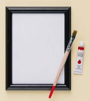 Empty white picture frame with paint tube and paintbrush