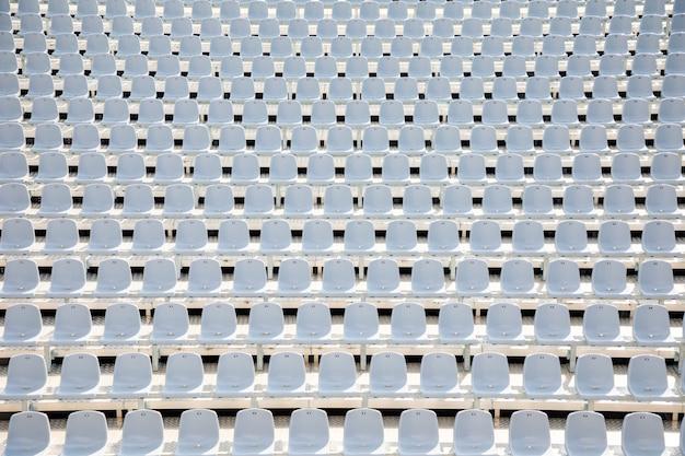 Empty white plastic seats in a stadium