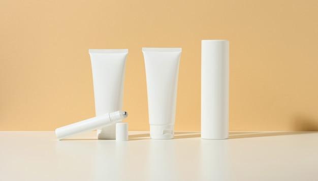 빈 흰색 플라스틱 튜브, 얇은 롤러, 베이지색 배경에 병. 브랜드 젤, 크림, 로션, 샴푸용 화장품. 에코 화장품을 모의