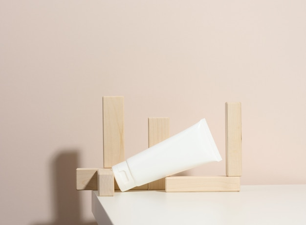 Empty white plastic tubes for cosmetics on a beige background with wooden blocks. packaging for cream, gel, serum, advertising and product promotion, mock up