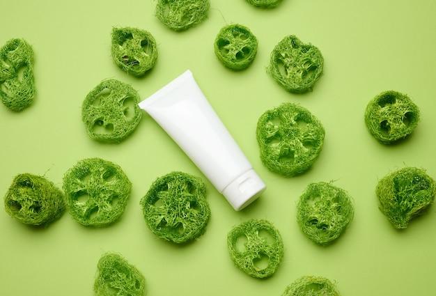 녹색 배경에 화장품을 위한 빈 흰색 플라스틱 튜브. 크림, 젤, 혈청, 광고 및 제품 판촉용 포장, 평면도