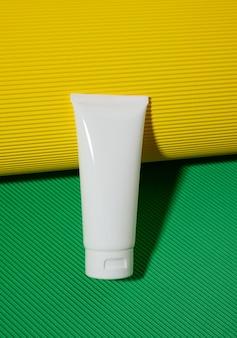 녹색 노란색 배경에 화장품용 빈 흰색 플라스틱 튜브. 크림, 젤, 혈청, 광고 및 제품 판촉용 포장, 모형