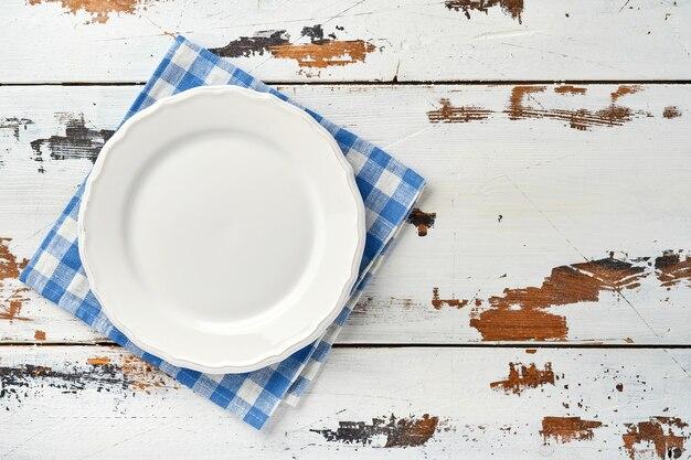 Пустая белая тарелка и синее полотенце над старым белым фоном деревянного стола для рецепта или меню.