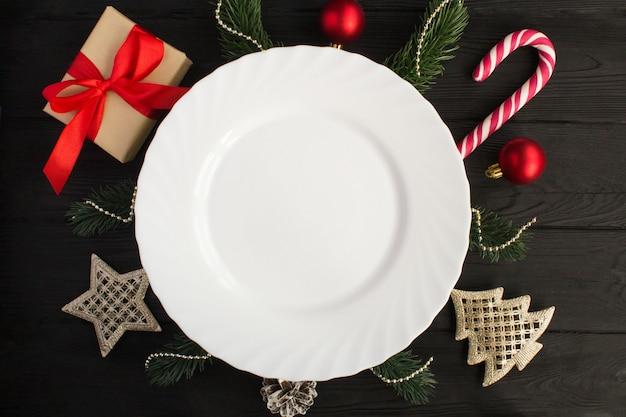 空の白い皿と黒い木の表面にクリスマスの組成物。上面図。スペースをコピーします。