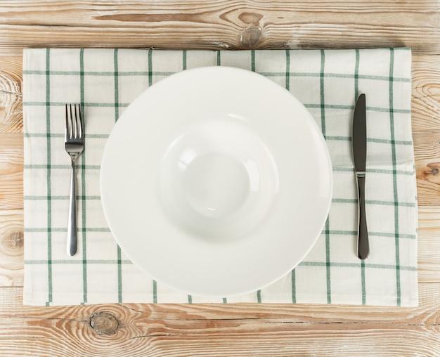 空の白いプレートと木製のテーブルトップビューのカトラリー