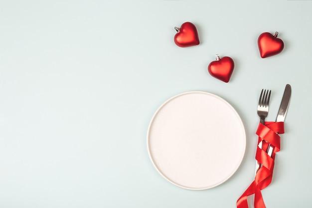 Пустая белая тарелка и столовые приборы. тема дня святого валентина. место для текста.