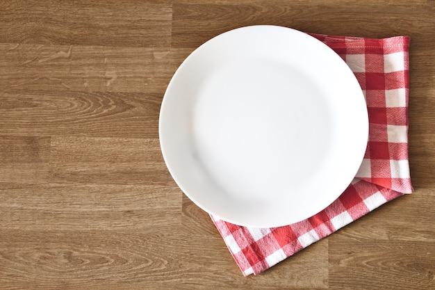 나무 테이블 배경 위에 빈 흰색 접시와 수건. 공간과 식사 장소를 복사합니다.