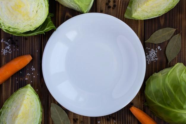 空の白いプレート、茶色の木製の背景にキャベツとニンジン。健康的な食材。上面図。コピースペース。