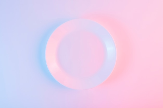 An empty white plate over colored background
