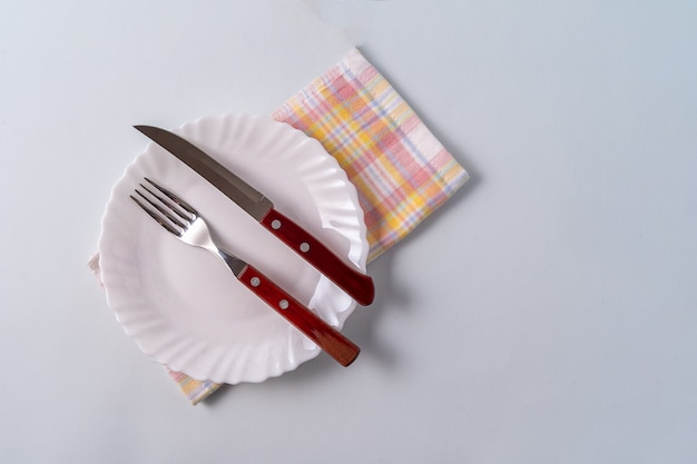 An empty white plate and cutlery on top of a napkin