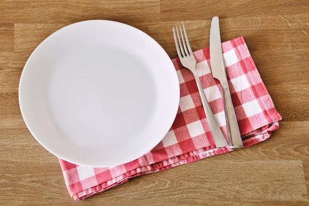 나무 테이블 배경 위에 빈 흰색 접시 포크 나이프와 수건 복사 공간 및 식사 장소