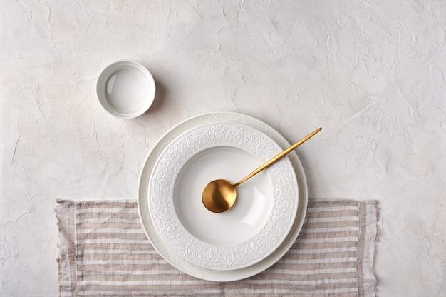 Пустая белая тарелка соуса, золотая ложка на салфетке, кухонная утварь на светло-серой столешнице
