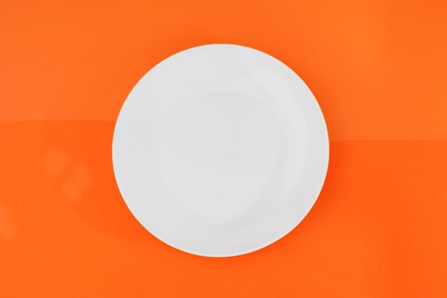 Empty white plate isolated on orange background. view from above.